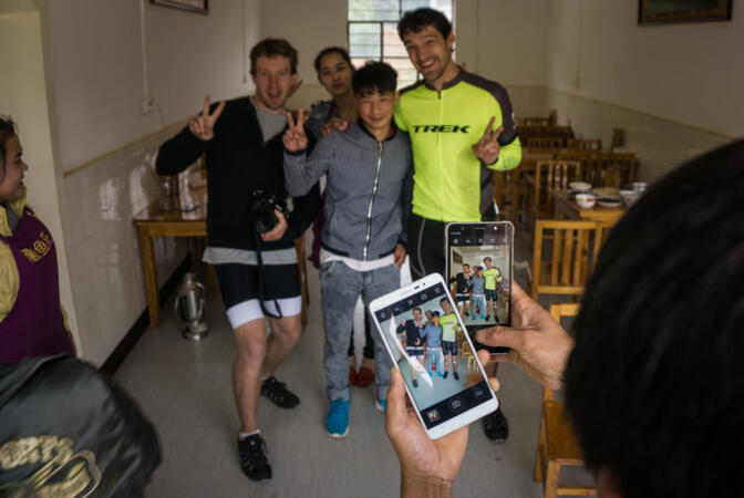 Will and Stew pose for ubiquitous smartphone pictures with local folks at a roadside lunch stop in Shiping, China (photo credit: Kyle Seewald Hemes)