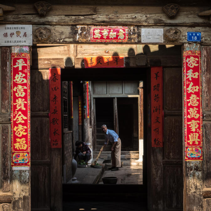 A man sweeps inside the Old City of Shiping, Yunnan province. The quiet, twisting streets of the old city are quite a contrast from the sprawling new development outside (photo credit: Will Stauffer-Norris)