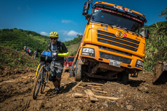 Kyle Hemes pushes his bike past giant Chinese trucks stuck on a steep, muddy back road (photo credit Will Stauffer-Norris)
