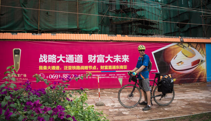 Will inspecting a Chinese billboard announcing a new high speed rail which will pass through the border town of Mohan (photo credit: Kyle Seewald Hemes)