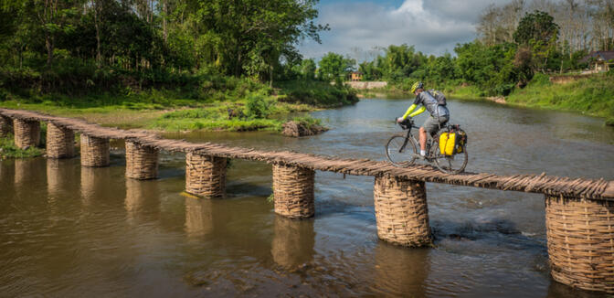 Kyle balances his loaded bike across a bamboo bridge in rural Luang Namtha (photo credit: Will Stauffer-Norris)