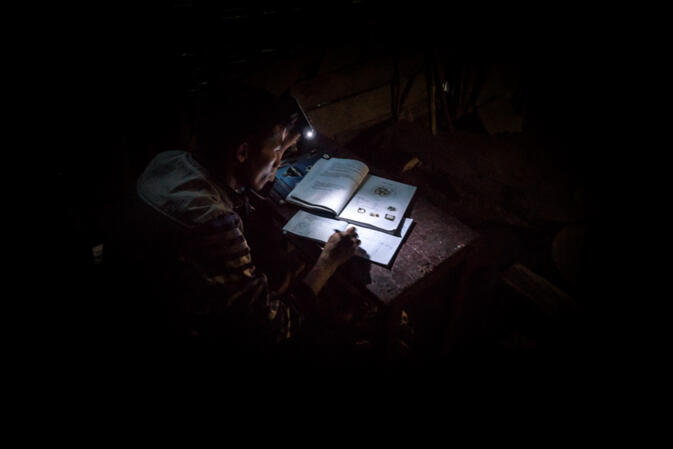 A man does his homework by the light on his cellphone in the remote Hmong village of Ban Sam Soun, Laos. This village has no running water or electricity, yet is located on a paved road next to power lines (photo credit: 	Will Stauffer-Norris)