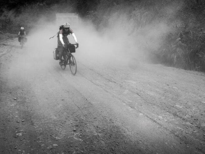 Kyle rides past clouds of dust kicked up by heavy trucks carrying rocks to the dam site of Nam Ou #6 (photo credit: Will Stauffer-Norris)