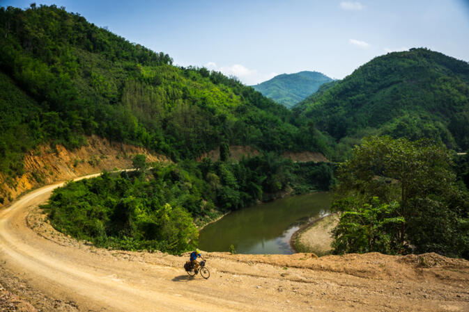 Nearing Luang Prabang, Will pushes up the dirt road along the Xuang River in Laos (photo credit: Kyle Seewald Hemes)