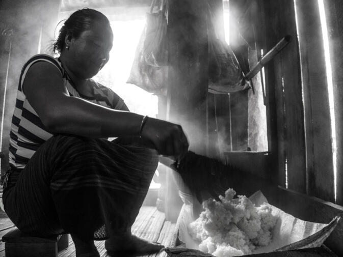 The wife of the village headman prepares fresh, steaming sticky rice for breakfast in Oudomxay province, Laos (photo credit: Simone Phillips)