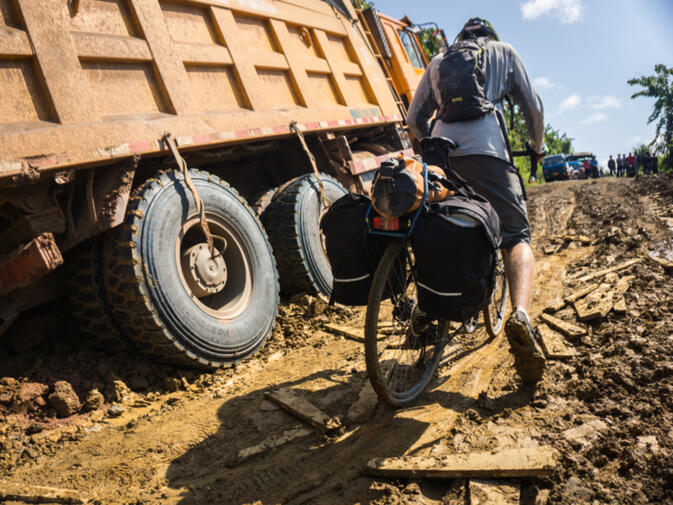 Will wades through the muck that has caught these heavy duty Chinese trucks after a rainstorm in Oudomxay province, Laos (image credit: Kyle Seewald Hemes)