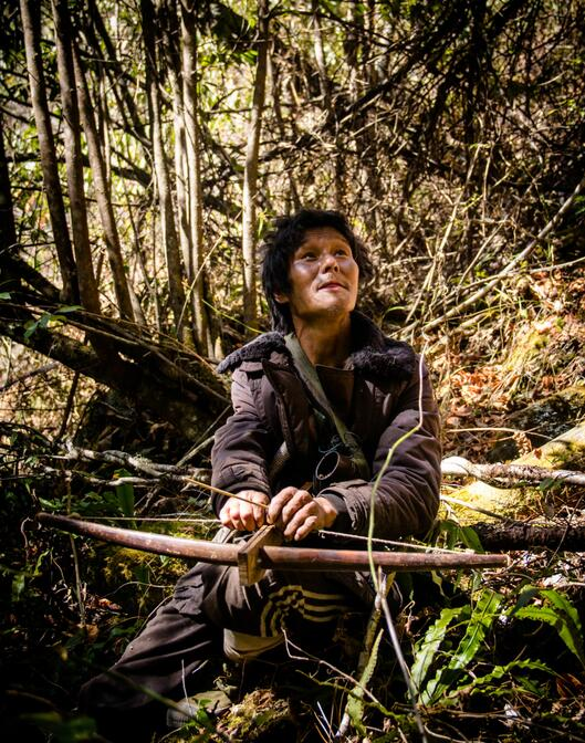 Yang Xin (杨新) scouting for small birds while preparing a wooden crossbow.
