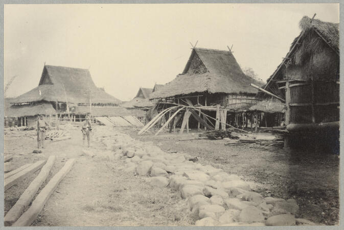 Village street with rocks and thatch roofed buildings March 1, 1922