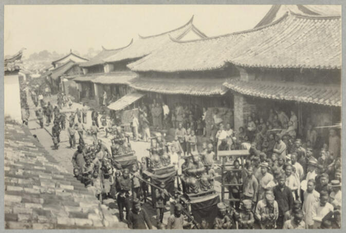 Crowded street procession with people carrying idols March 6, 1922