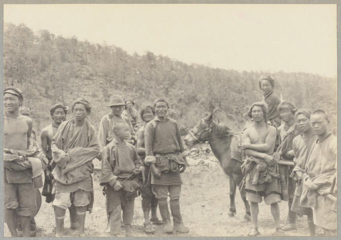 Group of people in native dress with two mounted on horses June 2, 1922