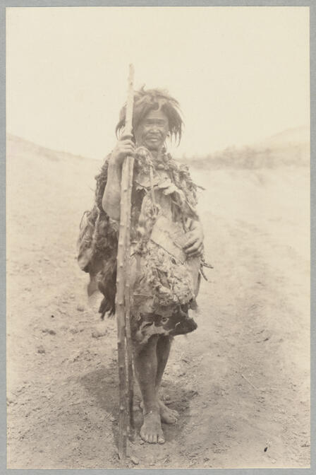 Full body view of man in native dress carrying sticks May 10, 1922