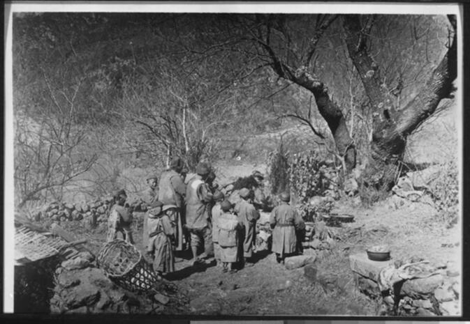 Naxi family performing a Muan bpo ceremony outdoors near Lijiang February 1931