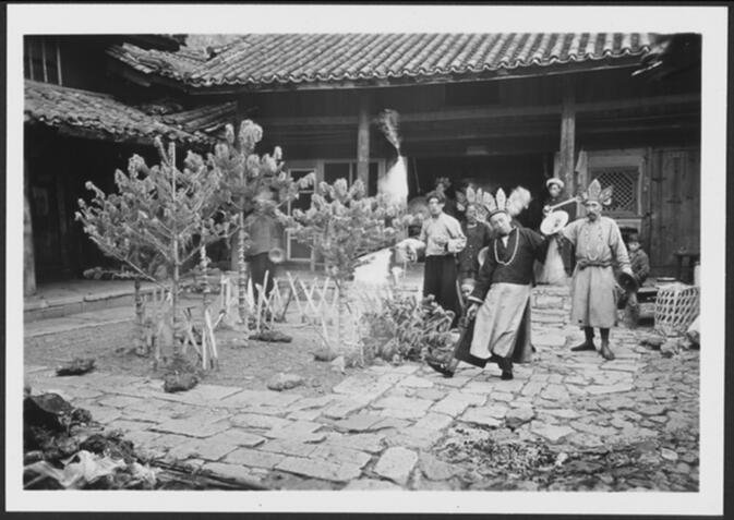 Naxi dto-mbas with headdresses, knives, and musical instruments performing a religious ceremony in the courtyard of Joseph Rock's house Undated