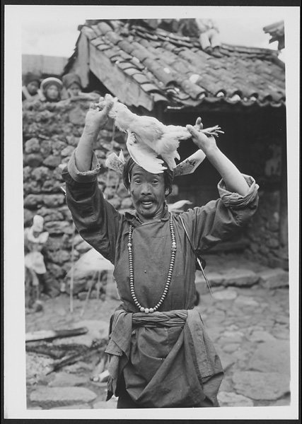 Naxi Llü-bu in a trance wearing a red turban with prayer papers and offering a chicken near Lijiang 1931