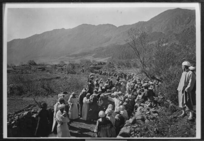 Members of a Naxi funeral procession carrying a coffin out of the village of Nv-lv-k'ö with the Lijiang Snow Range in the background Undated