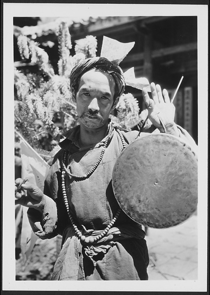 Naxi Llü-bu with a gong and wearing a red turban with prayer papers about to go into a trance near Lijiang 1931