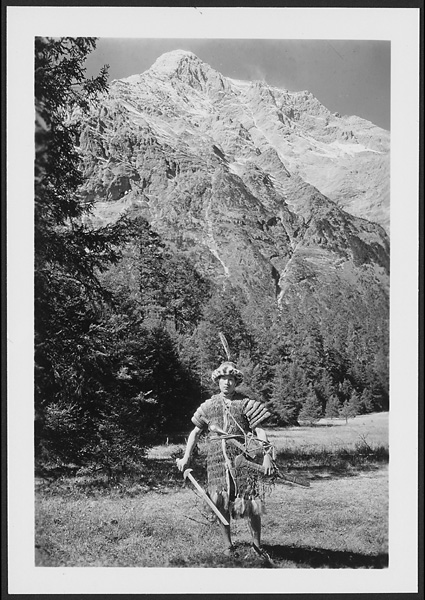Naxi man with drawn sword wearing traditional Hli-khin warrior's armor made of rhinoceros blades lacquered red and helmet of iron segments at the foot of the Lijiang snow range Undated