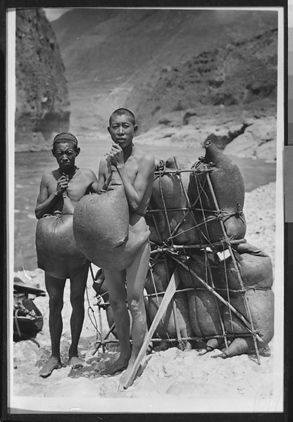 Two Naxi swimmers wearing inflated goatskin floats standing next to a goatskin raft used as a ferry for crossing the Yangtze River Undated