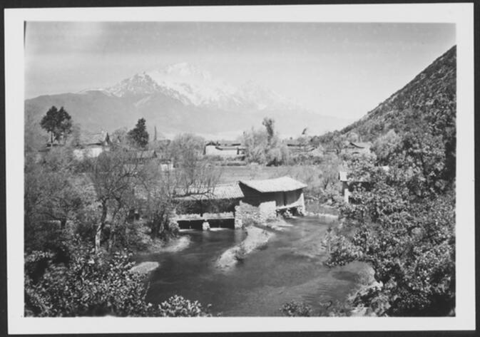 Village and mill on a river near Lijiang with Yulongxue Shan in background Undated
