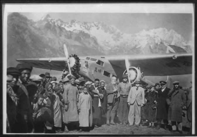 Joseph Rock (in light-colored suit) and crowd standing in front of the Kunming, a Ford Tri-motor airplane, at the landing field north of Lijiang 1936