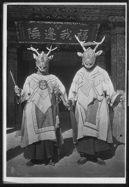 Two masked dancers representing deer or Showa spirits posing with daggers at Yung-ning Lamasery during the Dtor-ma (gtor-ma) Festival 1931