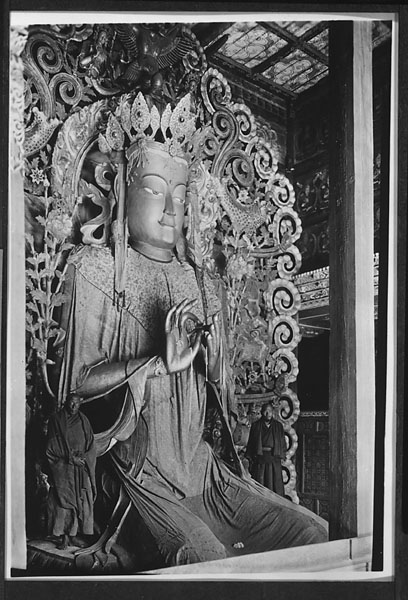 Giant gilt clay statue of Maitreya Buddha flanked by two lama priests in the Maitreya Hall at Yung-ning Lamasery 1931 or 1932