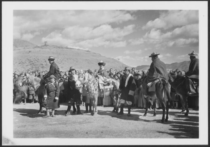 Lu zo, a young tulku or recognized reincarnation of a Bodhisattva, mounted on a horse with decorative trappings and surrounded by attendant lamas and on-lookers during his installation as Lhasa Incarnation in Yung-ning 1931 or 1932