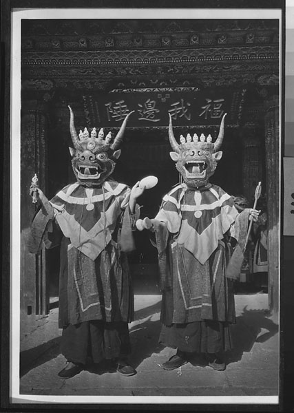 Two masked dancers representing central and northern gShin-rje sngon-po, the blue Lords of the Dead, with scepter, scull cup, drum, and arrow at Yung-ning Lamasery during the Dtor-ma (gtor-ma) Festival 1931