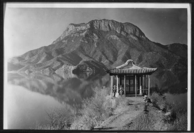 Two men at a pavilion on the island of Nyo-ro-p'u in Yung-ning Lake with Lion Mountain in the background Undated