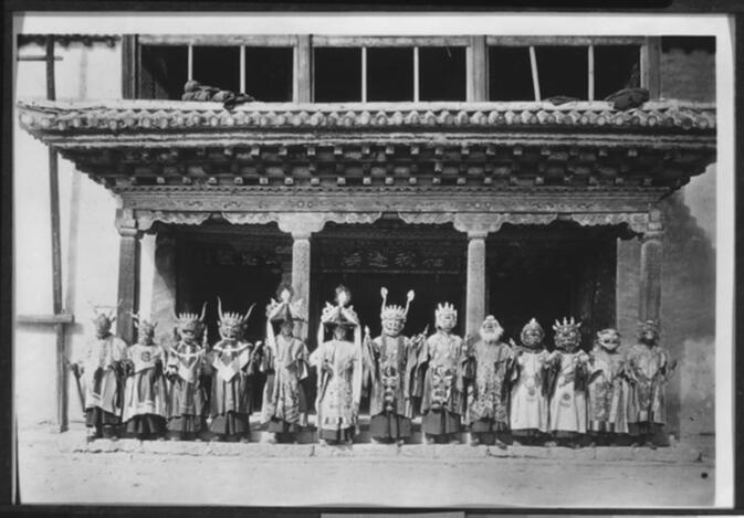 Eleven masked dancers and two Black Hat dancers in front of the main chanting hall at Yung-ning Lamasery during the Dtor-ma (gtor-ma) Festival 1931