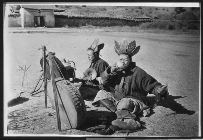 Two Nda-pa priests with musical instruments and other ritual objects performing a ceremony on the plain in front of the Yung-ning Lamasery Undated