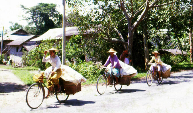Dai women cycling home from the fields west of Ruili