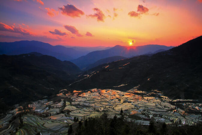 The terraced mountains of Yuanyang reflect the sunset