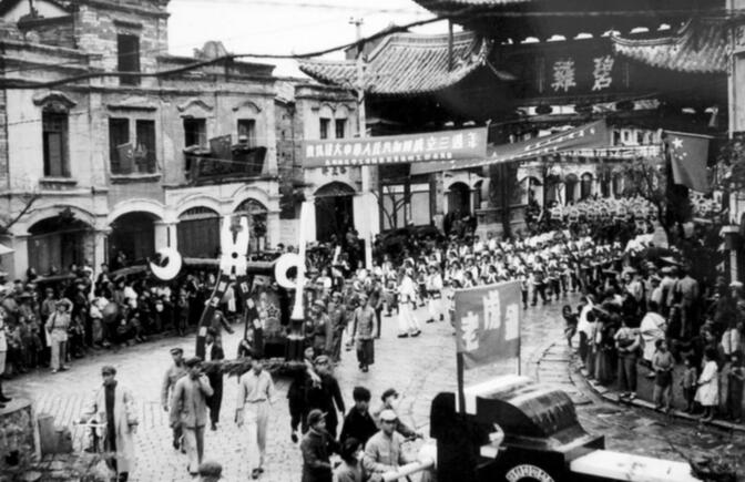 A National Day parade passes under Biji Gate in 1952 (image credit: CCWB)