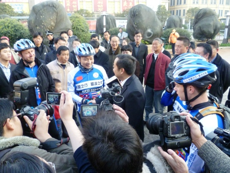 Jin Feibao (center, in riding gear), receiving good-luck handshake from Mayor Zhang Zulin