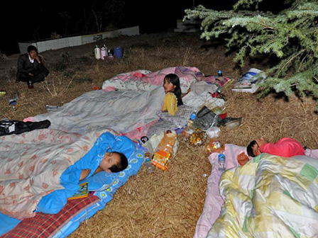 A family sleeps outside after a magnitude 5.5 earthquake struck Yunnan Dali-Bai Autonomous Prefecture