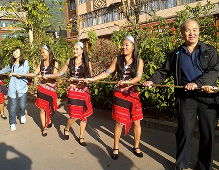 Members of the Ximeng Song and Dance Troupe, along with Chinese tourists, pull the drum down the street