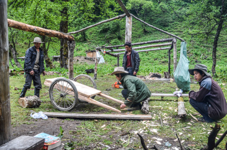 Local workers building a wheelbarrow under the support beams of a temporary refuge