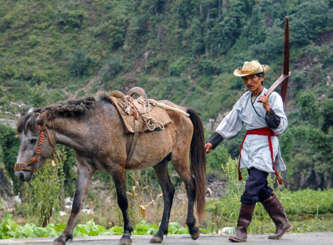 En route to the market, Lisu man with his crossbow