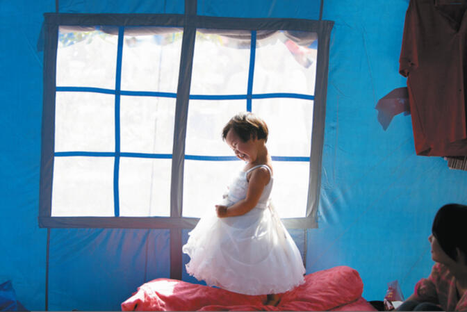 A girl plays inside a relief tent in earthquake-ravaged Ludian County