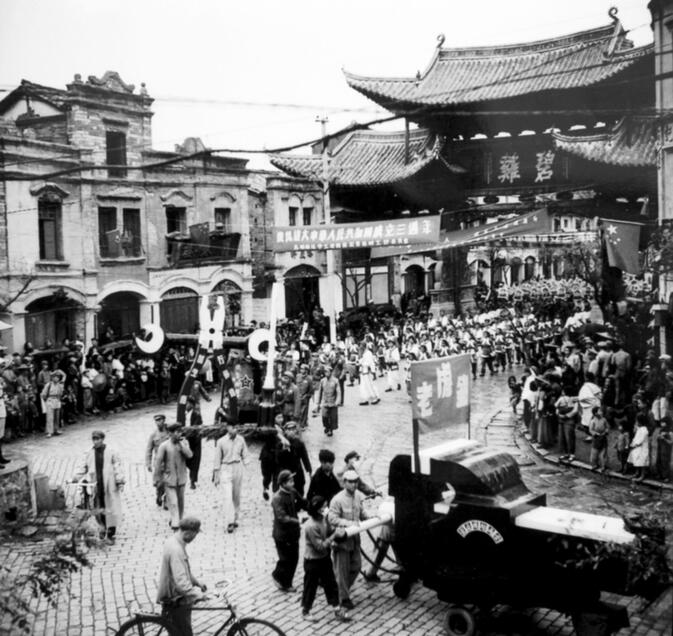 A National Day parade passes under Biji Gate in 1952