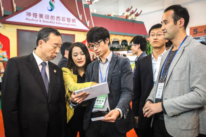 Yunnan's former vice-governor, Liu Ping (far left), visits with S-MAX founder Yang Jie (far right) at the joint S-MAX/GoKunming exhibit
