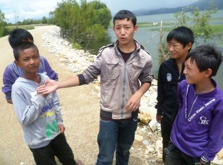 Bai youth hanging out lakeside