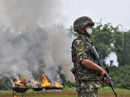 A soldier stands guard as seized drugs are burned in Dehong
