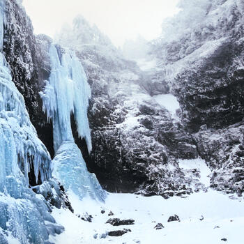 A 30-meter waterfall frozen in place during the winter on Jiaozi Snow Mountain