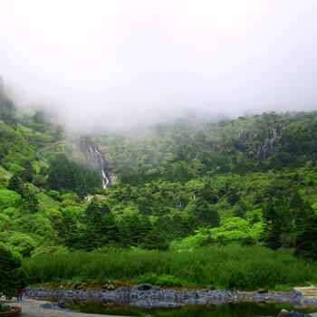 Waterfalls pour down the slopes of Jiaozi Snow Mountain near the park entrance