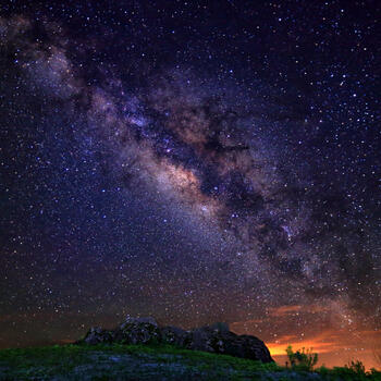 The Milky Way sparkles above a butte on Jiaozi Snow Mountain