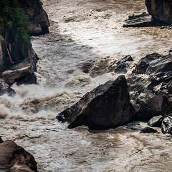 A boulder the size of a house withstands the deluge in Tiger Leaping Gorge, China (image credit: Yereth Jansen)