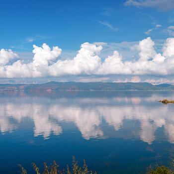 Springtime clouds reflected in the waters of Fuxian Lake in Yunnan province