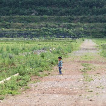 A little boy surveys a field outside of Dali Old Town